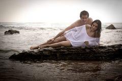 Junge schöne Paare, die am Strand flirten lizenzfreie stockbilder