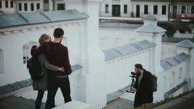 Junge schöne Paare, die unten auf die Treppe gehen Männlicher Fotograf, der Fotos des stilvollen Mannes und der Frau macht stock video