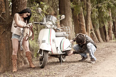Junge schöne Paare mit Roller entlang Schotterweg Lizenzfreies Stockbild