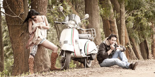 Junge schöne Paare mit Roller entlang Schotterweg Stockbilder