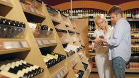 Junge schöne Paare wählen Wein unter Verwendung des Mobiltelefons im Supermarkt stock video footage