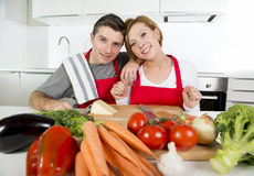 Junge schöne Paare, welche zu Hause die Küche vorbereitet Gemüsezusammen lächeln des salats glücklich bearbeiten Lizenzfreie Stockfotos