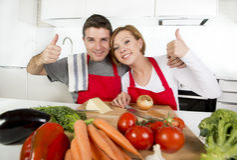Junge schöne Paare, welche zu Hause die Küche vorbereitet Gemüsezusammen lächeln des salats glücklich bearbeiten Lizenzfreies Stockfoto