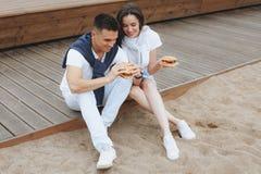 Junge schöne positive Paaressen hambergers, die auf bea sitzen stockfotografie