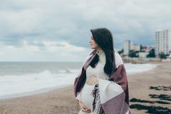 Junge schöne pragnant Frau, die nahe Meer am Strand aufwirft Lizenzfreie Stockfotos