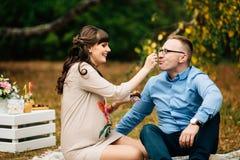 Junge schöne reizende Zufuhren der schwangeren Frau ihr hübscher Ehemann mit Kuchen auf Picknick Lizenzfreies Stockfoto