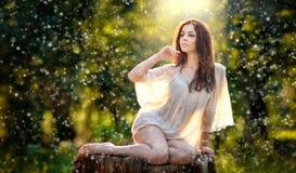 Junge schöne rote Haarfrau, die eine transparente weiße Bluse aufwirft auf einem Stumpf in einem grüner Waldmodernen sexy Mädchen Lizenzfreie Stockfotos