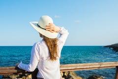Junge schöne schlanke Frau mit dem langen Haar, das sunhat vom Wind in boho Art hält, kleidet in dem Uferschauen und dem Meer Stockbilder
