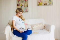 Junge schöne schwangere Frau, die auf Sofa mit einem Buch sitzt Lizenzfreie Stockfotografie