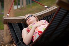 Junge schöne schwangere Frau, die in der Hängematte sich entspannt Lizenzfreie Stockfotografie