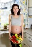Junge schöne schwangere Frau, die einen Korb von Früchten hält lizenzfreie stockfotos