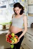 Junge schöne schwangere Frau, die einen Korb von Früchten hält stockbild