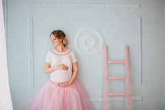 Junge schöne schwangere Frau, die nahe Fenster aufwirft Stockbild