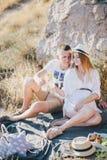 Junge schöne schwangere Frau, die Picknick mit ihrem Ehemann auf einem Berg nahe Meer hat Lizenzfreies Stockbild