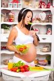 Junge schöne schwangere Frau mit einer Platte des Frischgemüsesalats Lizenzfreies Stockbild