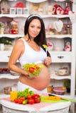 Junge schöne schwangere Frau mit einer Platte des Frischgemüsesalats Lizenzfreie Stockfotos
