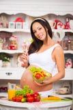 Junge schöne schwangere Frau mit einer Platte des Frischgemüsesalats Lizenzfreie Stockbilder