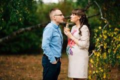 Junge schöne schwangere Frau reizend und ihr hübscher Ehemanngetränksaft Stockbilder
