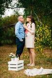 Junge schöne schwangere Frau reizend und ihr hübscher Ehemanngetränksaft Lizenzfreies Stockbild
