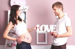 Junge schöne schwangere Frau und ihr hübscher Ehemann lizenzfreie stockfotos