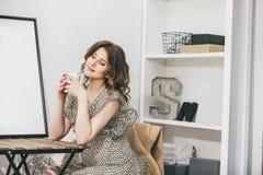 Junge schöne schwangere Frau zu Hause am Tisch mit einem Becher I Lizenzfreie Stockfotos
