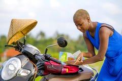 Junge schöne schwarze afroe-amerikanisch touristische Frau mit dem Rollermotorrad, das zur Straßenkarte herein sucht die Erforsch stockfoto