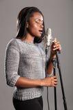 Junge schöne schwarze Frau, die im Mikrofon singt Stockfotografie