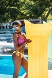 Junge schöne schwarze Frau, die mit aufblasbarer Matratze am Poolside aufwirft lizenzfreies stockfoto
