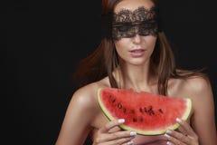 Junge schöne sexy Frau mit dunkler Spitze auf Augen entblößen die Schultern und Hals und halten Wassermelone, um den Geschmack zu Stockbild