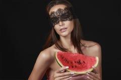 Junge schöne sexy Frau mit dunkler Spitze auf Augen entblößen die Schultern und Hals und halten Wassermelone, um den Geschmack zu Stockfotografie