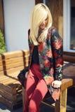 Junge schöne stilvolle Frau, die auf der Straße in Blumen gedruckt aufwirft lizenzfreie stockfotografie