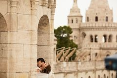 Junge schöne stilvolle Paare Jungvermählten, die durch das Fisherman& x27 küssen; s-Bastion in Budapest, Ungarn lizenzfreie stockfotos