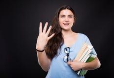 Junge schöne Studentenfrau, die vier zählt lizenzfreie stockfotografie