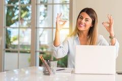 Junge schöne Studentenfrau mit Laptop bei Tisch, zu Hause lizenzfreies stockbild