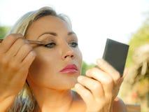 Junge schöne und attraktive blonde Frau mit blauen Augen Make-up mit der Bürste überarbeitend, die den Lidschatten herein hält kl stockfotos