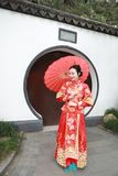 Junge, schöne und elegante Chinesin, die das rote Kleid der Seide einer typischen chinesischen Braut, geschmückt mit goldenem Pho lizenzfreie stockbilder