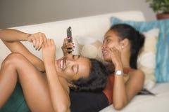 Junge schöne und glückliche asiatische Freundinpaare oder -schwestern, die das Internet-Social Media hat Spaß zusammen mit Handy  stockfotos