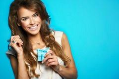 Junge schöne und glückliche Frau mit einem Geschenk Lizenzfreies Stockfoto
