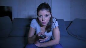 junge schöne und glückliche lateinische Frau auf ihrem 30s, das Fernsehdirektübertragung aufpassende Fernsehsendung der Wohnzimme lizenzfreies stockfoto