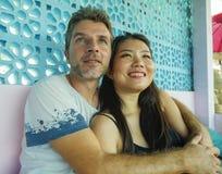 Junge schöne und glückliche Mischethniepaare beim Liebeslächeln nett zusammen mit hübschem kaukasischem Mann und schönem Asi stockfotos