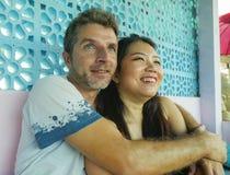 Junge schöne und glückliche Mischethniepaare beim Liebeslächeln nett zusammen mit hübschem kaukasischem Mann und schönem Asi lizenzfreies stockfoto