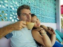 Junge schöne und glückliche Mischethniepaare in der Liebe entspannt zusammen mit trinkendem Kaffee des hübschen kaukasischen M lizenzfreies stockfoto