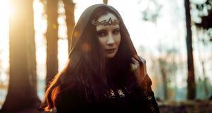Junge schöne und mysteriöse Frau im Holz, im schwarzen Mantel mit Haube, im Bild der Waldelfe oder in der Hexe lizenzfreies stockfoto