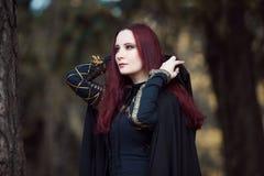 Junge schöne und mysteriöse Frau im Holz, im schwarzen Mantel mit Haube, im Bild der Waldelfe oder in der Hexe lizenzfreie stockbilder
