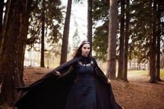 Junge schöne und mysteriöse Frau im Holz, im schwarzen Mantel mit Haube, im Bild der Waldelfe oder in der Hexe lizenzfreie stockfotografie