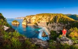 Junge Schönheit auf dem azurblauen Strand des Hintergrundes mit felsigen Bergen und klarem Wasser Lizenzfreie Stockfotografie
