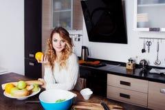 Junge Schönheit auf der Küche hält eine Orange in der Hand, wählt gesunde Diät Stockbild