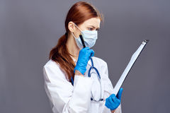 Junge Schönheit auf einem grauen Hintergrund mit Gläsern hält einen Ordner mit Dokumenten und Stift, Doktor, Medizin Stockbild