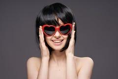 Junge Schönheit auf einem schwarzen Hintergrund in der Sonnenbrille im Herzen von Herzen Lizenzfreies Stockfoto