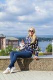 Junge Schönheit in den Blue Jeans, die in der Sommerstraßengleichheit sitzen Stockbilder